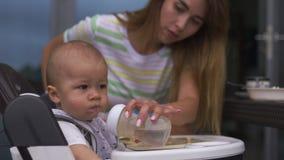 Madre joven que alimenta a su hijo del bebé que se sienta en un asiento del niño - escena caliente del verano del color de los va almacen de metraje de vídeo