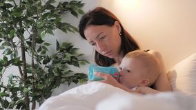 Madre joven que alimenta a su hijo del beb? con una botella de leche en casa almacen de metraje de vídeo