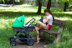 Madre joven que amamanta a su bebé lindo, celebrando al niño suavemente en manos y sentándose en el banco de parque, cochecito ve imagen de archivo libre de regalías