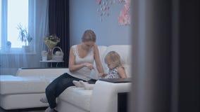 Madre joven que aprende al niño lindo cómo utilizar la tableta imágenes de archivo libres de regalías