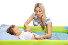 Madre joven que cambia un pañal en su hijo del bebé Fotos de archivo