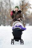 Madre joven que camina con el bebé en cochecito en invierno Imagen de archivo