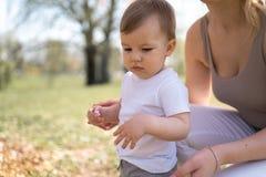Madre joven que camina con su hijo del ni?o del beb? en un parque debajo de los ?rboles de Sakura imagenes de archivo