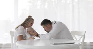 Madre joven que celebra al bebé mientras que el pediatra escucha su pecho en su oficina en el hospital almacen de metraje de vídeo