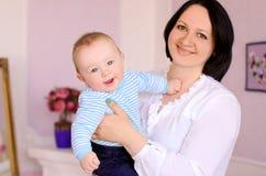 Madre joven que celebra al hijo alegre del bebé fotos de archivo libres de regalías