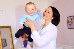 Madre joven que celebra al hijo alegre del bebé imagen de archivo