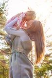 Madre joven que celebra a la hija linda de la niña pequeña en sus brazos y que la levanta para arriba en el aire, ambos que ríen Imagenes de archivo