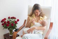Madre joven que celebra a su bebé, brestfeeding lo, asistiendo fotos de archivo
