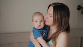 Madre joven que celebra a su niño durmiente recién nacido Familia en casa, mamá y bebé en el dormitorio, beso del mothe besándola almacen de metraje de vídeo