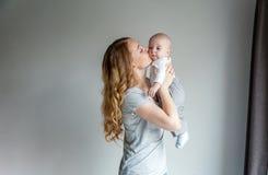 Madre joven que celebra a su niño recién nacido Fotos de archivo