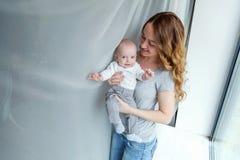 Madre joven que celebra a su niño recién nacido Foto de archivo libre de regalías