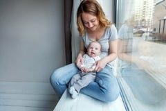 Madre joven que celebra a su niño recién nacido Fotografía de archivo