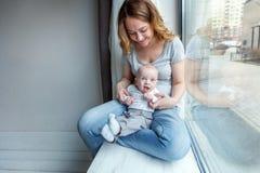 Madre joven que celebra a su niño recién nacido Fotografía de archivo libre de regalías
