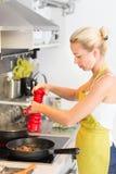 Madre joven que cocina en casa Imagen de archivo libre de regalías