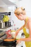 Madre joven que cocina en casa Fotos de archivo libres de regalías