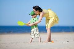 Madre joven que enseña a su hijo a jugar a tenis Imágenes de archivo libres de regalías