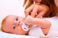 Madre joven que intenta dar el maniquí del `s del bebé   Fotografía de archivo libre de regalías