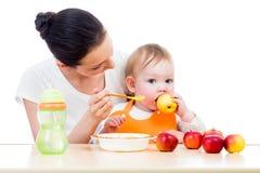 Madre joven que introduce a su bebé. Concepto de la nutrición sana. Fotos de archivo libres de regalías