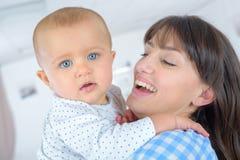 Madre joven que juega con el bebé en la hoja de cama Fotos de archivo