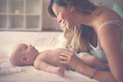 Madre joven que juega con su bebé en cama Madre que disfruta de i foto de archivo