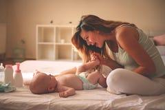 Madre joven que juega con su bebé en cama Goce de la madre foto de archivo libre de regalías