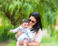Madre joven que juega con su bebé en el jardín Fotografía de archivo libre de regalías