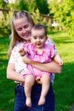 Madre joven que juega con su bebé en el parque imagen de archivo