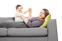 Madre joven que juega con su hija del bebé imagenes de archivo