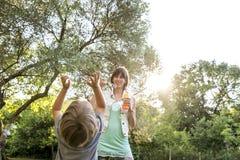 Madre joven que juega con su niño al aire libre Fotos de archivo