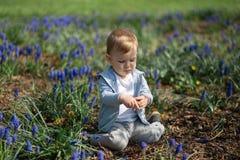 Madre joven que juega y que habla con un hijo del beb? en un campo del muscari en la primavera - d?a soleado - jacinto de uva - R foto de archivo