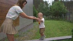 Madre joven que juega y que se divierte con sus hermanos del hijo del bebé en un jardín con los juguetes - color caliente de los  metrajes
