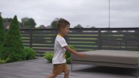 Madre joven que juega y que se divierte con sus hermanos del hijo del bebé en un jardín con los juguetes - color caliente de los  almacen de metraje de vídeo
