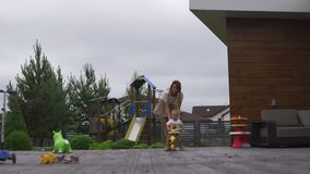 Madre joven que juega y que se divierte con sus hermanos del hijo del bebé en un jardín verde con las bicicletas - valores famili metrajes