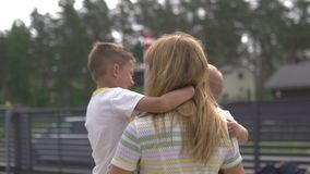 Madre joven que juega y que se divierte con sus hermanos del hijo del bebé en un jardín verde - verano caliente del color de los  almacen de metraje de vídeo