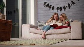 Madre joven que lee un libro a su hija linda almacen de metraje de vídeo