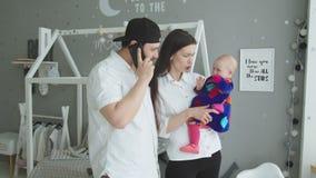 Madre joven que menea a la niña pequeña en las manos en casa almacen de metraje de vídeo
