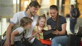 Madre joven que muestra a su familia algo interesante en tableta mientras que se están sentando en salón de la salida del aeropue