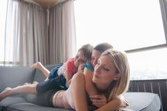 Madre joven que pasa tiempo con los niños en el piso Imagen de archivo