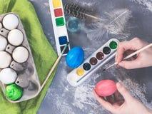 Madre joven que pinta los huevos de Pascua Foto de archivo