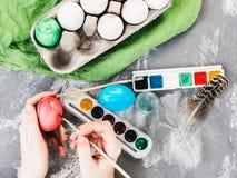 Madre joven que pinta los huevos de Pascua Imagen de archivo