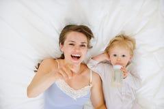 Madre joven que pone con el bebé en cama Fotos de archivo