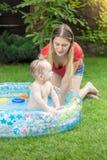 Madre joven que se sienta al lado de su natación del bebé en piscina inflable en el patio trasero fotografía de archivo libre de regalías