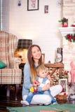 Madre joven que se sienta con la pequeña hija en el sitio adornado para la Navidad Foto de archivo