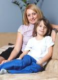 Madre joven que se sienta en el sofá con su hijo Fotografía de archivo libre de regalías