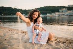 Madre joven que se sienta en la playa con el hijo de un a?o del beb? Muchacho que abraza, sonriendo, riendo, d?a de verano Ni?ez  foto de archivo libre de regalías