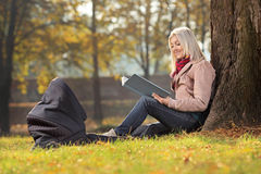 Madre joven que se sienta en un parque y que lee una historia a su bebé Imagenes de archivo
