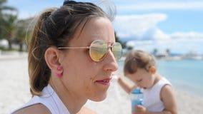 Madre joven que se sienta en una playa como sus juegos del dauhter metrajes