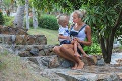 Madre joven que se sienta y que habla con su niño Imagen de archivo
