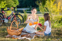 Madre joven que tiene comida campestre por el río con la hija Madre po Imágenes de archivo libres de regalías