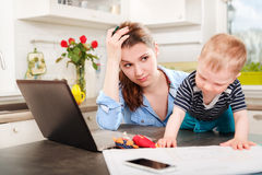 Madre joven que trabaja con su bebé Foto de archivo libre de regalías